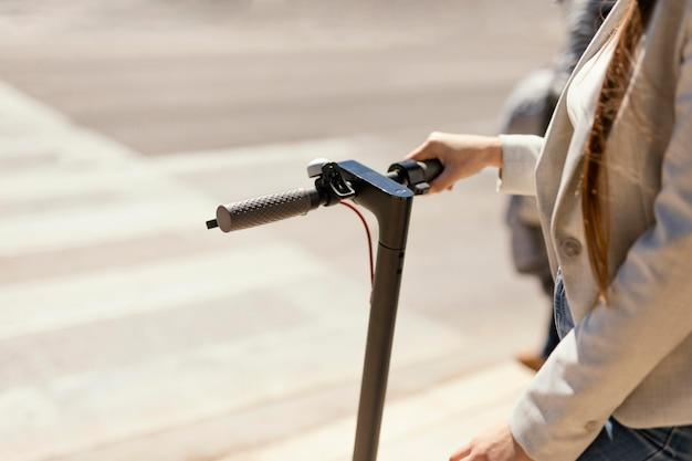 젊은 여자는 도시에서 전기 스쿠터 타기