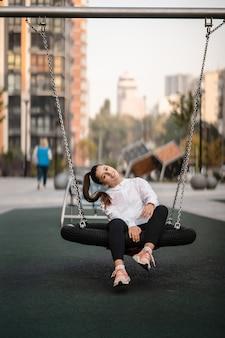 若い女性は遊び場でブランコに乗る。