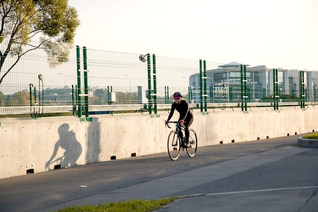 日没時に自転車に乗る若い女性