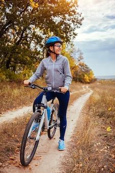 秋のフィールドで自転車に乗る若い女性