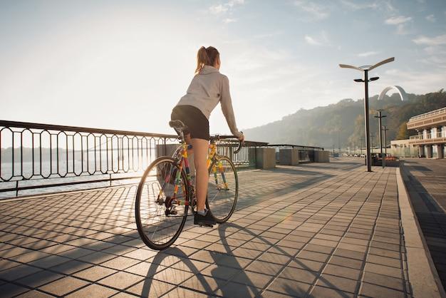 Молодая женщина, езда на велосипеде в утреннем городе