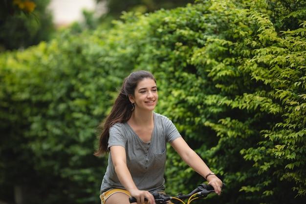 公園で自転車に乗る若い女性