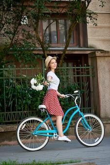青い都市の自転車に乗る若い女性