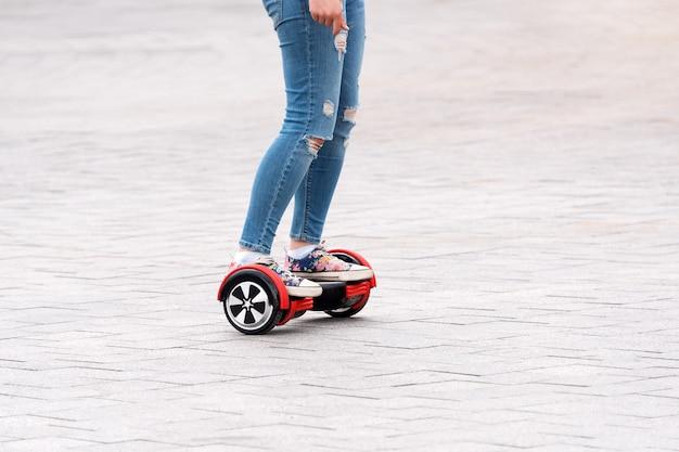 Молодая женщина катается на ховерборде на городской площади