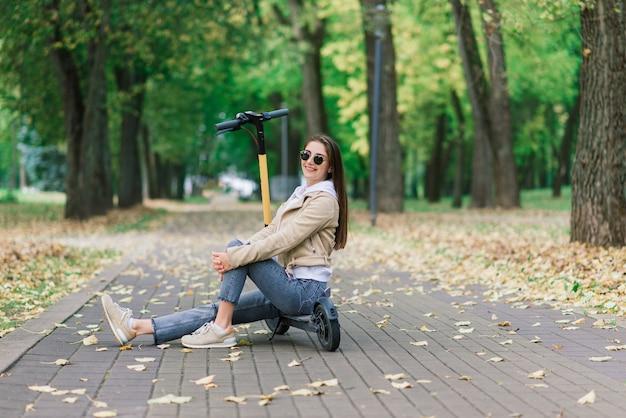 Молодая женщина на электросамокате в осеннем парке. зеленый транспорт, проблемы с пробками.