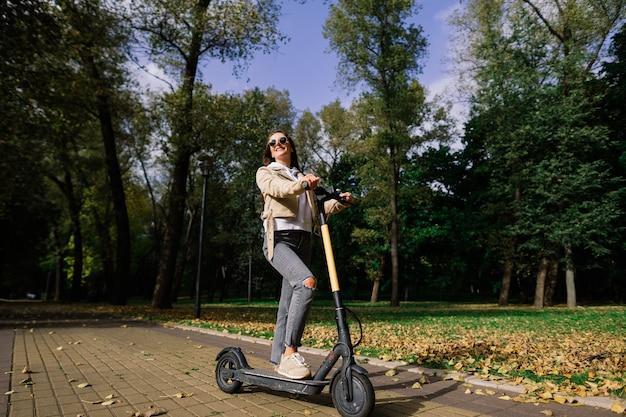 가을 공원에서 전기 스쿠터를 타고 젊은 여자. 녹색 교통, 교통 체증 문제.