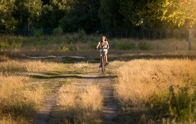 Young woman riding away on bicycle at meadow
