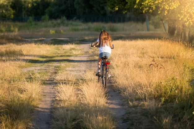 Young woman riding bicycle on dirt road at meadow