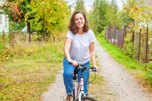 屋外の夏の都市公園で自転車に乗る若い女性