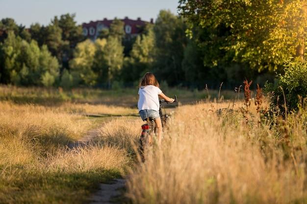 Young woman riding bicycle at meadow on dirt road at sunset