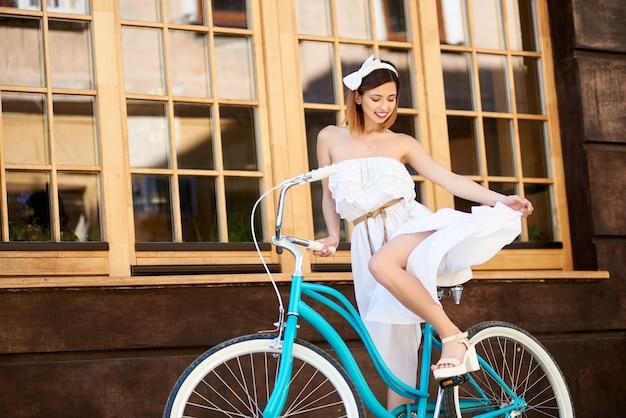 青い自転車に屋外で乗る若い女性
