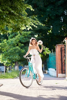 Young woman riding blue city bicycle outdoor