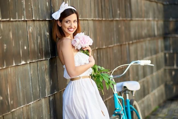 Молодая женщина, езда синий городской велосипед на открытом воздухе