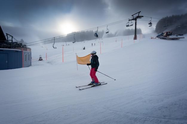 Молодая женщина катается по горнолыжному склону на австрийском горнолыжном курорте