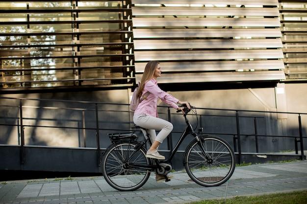 Молодая женщина, езда на велосипеде в городской среде