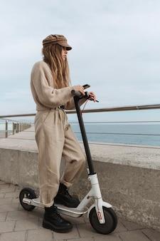 Giovane donna in sella a uno scooter elettrico