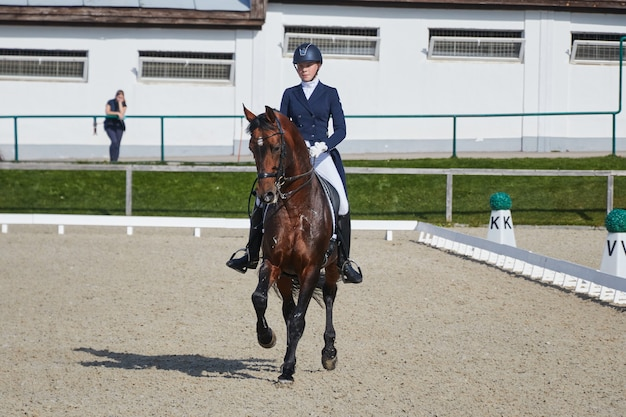 Young woman riding horse performs the task in equestrian competitions in dressage riding