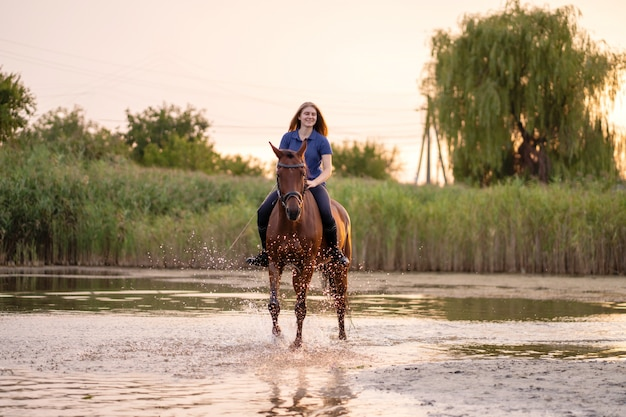 A young woman riding a horse on a shallow lake. a horse runs on water at sunset. care and walk with the horse. strength and beauty