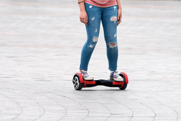 Young woman riding a hoverboard on the city square. new movement and transport technologies. close up of dual wheel self balancing electric skateboard. people on electrical scooter outdoors.