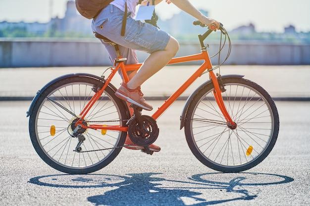 都市道路で自転車に乗って若い女性