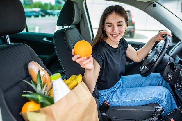 야외 주차장에 음식으로 가득 찬 쇼핑 카트를 타고 있는 젊은 여성. 주차장에서 젊은 여자, 자동차 부팅에 쇼핑을 로드 합니다. 쇼핑이 성공적으로 완료되었습니다