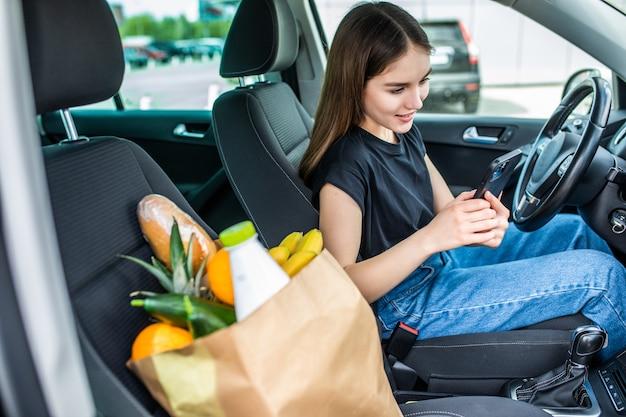 야외 주차장에서 음식으로 가득 찬 쇼핑 카트를 타고 있는 젊은 여성