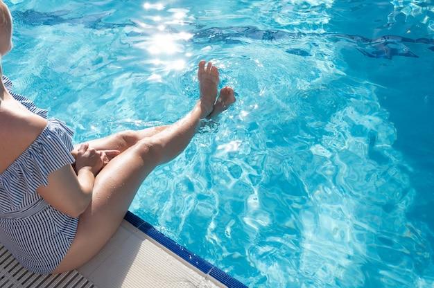 プールで彼女の足をすすぐ若い女性。