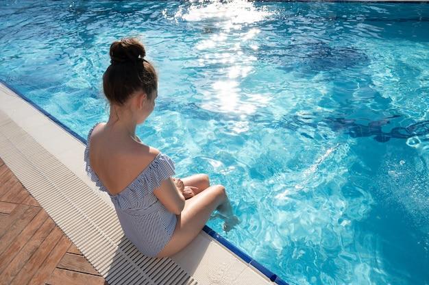 プールで彼女の足をすすぐ若い女性