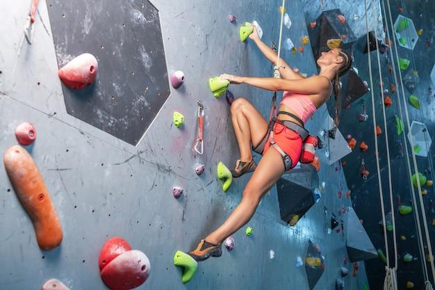 Young woman rock climber is climbing at inside climbing gym