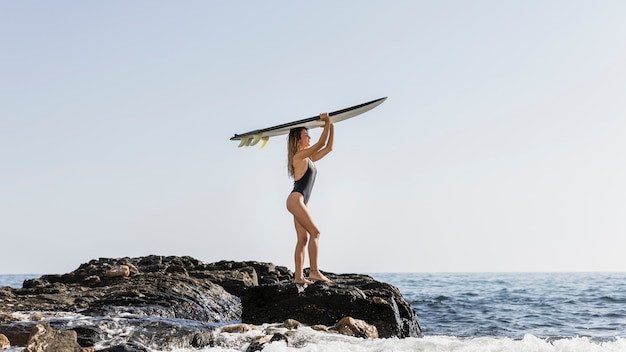 Young woman on rocky sea shore holding surfboard on head