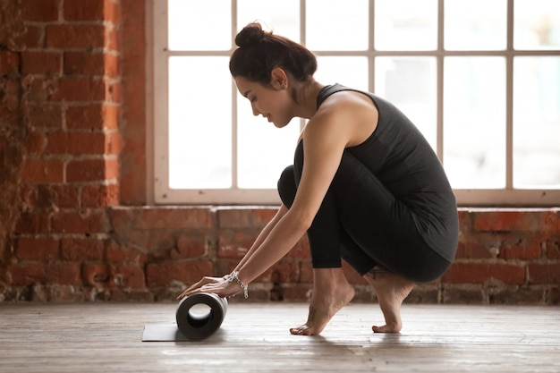 Young woman rolling exercise mat