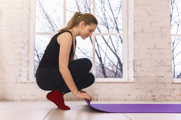 Young woman rolling her purple mat after a yoga class on  floor near a window,