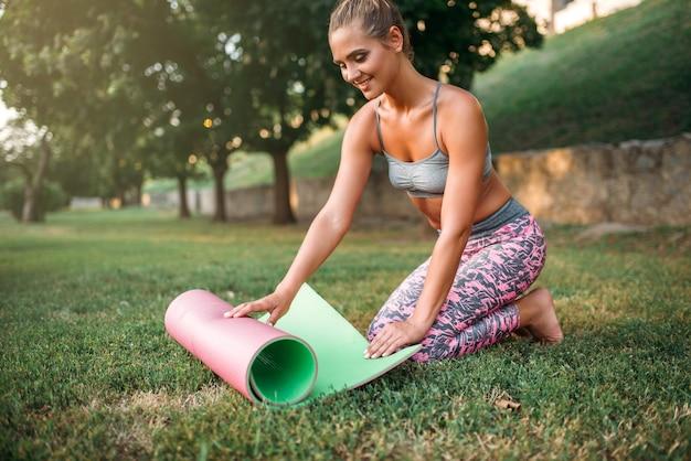 Коврик для йоги молодой женщины сворачивания в парке. утренняя гимнастика йога на открытом воздухе