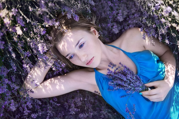 Young woman in the romantic blue dress relax in lavender fields. romantic girl lies in lavender flowers and dreams