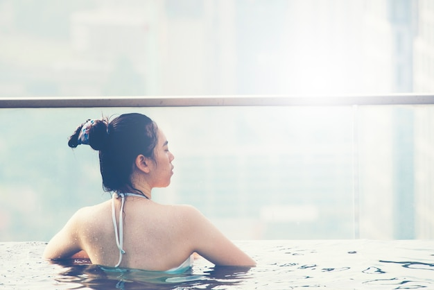 Young woman in a roof top swimming pool with beautiful city view