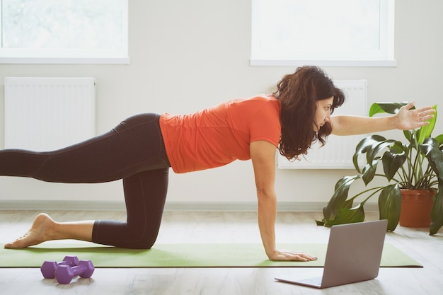 Young woman in the room doing yoga exercises Premium Photo