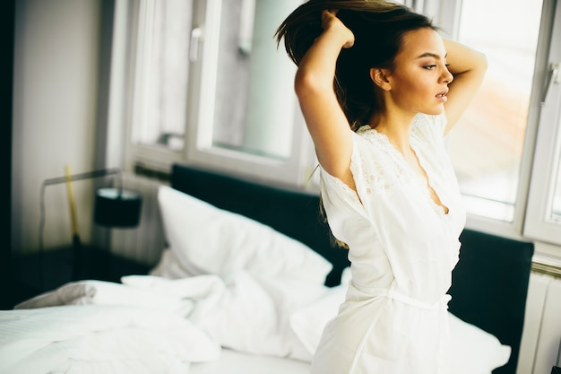 Young woman in the room gets out of bed