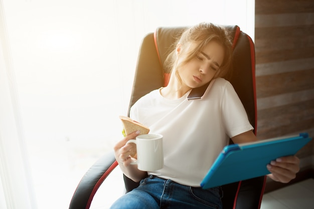 Young woman in room. talking on phone and using tablet in one hand. hold cup of teal or cofee with other. sit in chair at window. daylight.