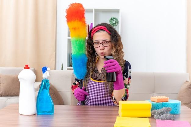 Giovane donna in guanti di gomma che tiene spolverino statico e spray detergente che sembra sicura seduta al tavolo con prodotti per la pulizia e strumenti in soggiorno luminoso