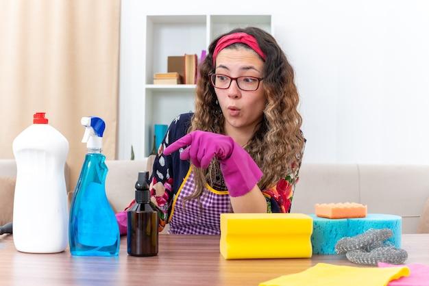 Giovane donna con guanti di gomma che sembra stupita e sorpresa seduta al tavolo con prodotti per la pulizia e strumenti in un soggiorno luminoso