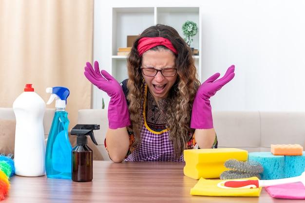 Giovane donna in guanti di gomma che sembra infastidita e irritata urlando e urlando con le braccia alzate seduta al tavolo con prodotti per la pulizia e strumenti in soggiorno luminoso