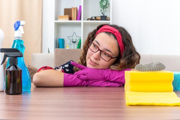Giovane donna in guanti di gomma che guarda da parte sorridente felice e positiva seduta al tavolo con prodotti per la pulizia e strumenti in un soggiorno luminoso