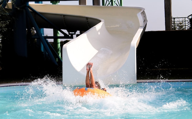 Young woman on rubber ring going down slide in aqua park. summer vacation concept