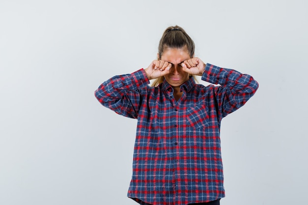 Young woman rubbing eyes in checked shirt and looking tired