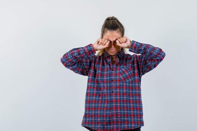 Молодая женщина протирает глаза в клетчатой рубашке и выглядит усталой