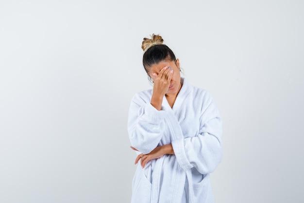 Молодая женщина потирает лоб в халате и выглядит измученной