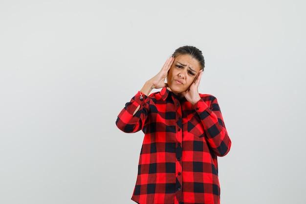 Giovane donna strofinando le tempie in camicia a quadri e guardando stanco, vista frontale.