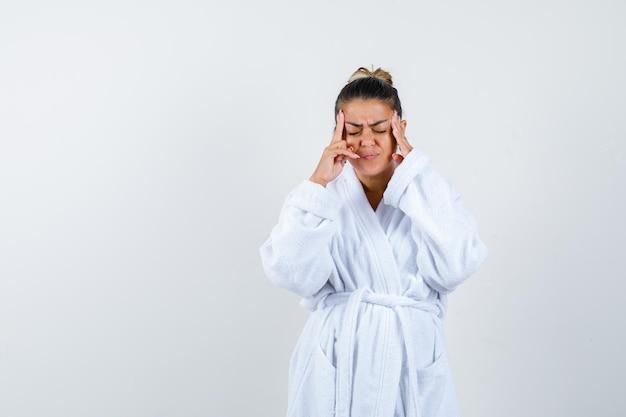 Молодая женщина потирает виски в халате и выглядит утомленной