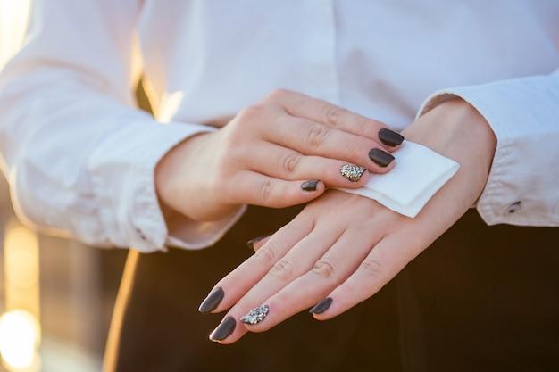 젊은 여자가 손의 피부에 젖은 냅킨을 문지릅니다.