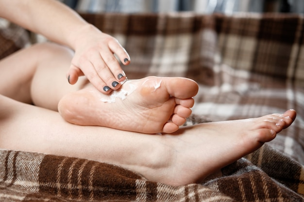 Young woman rubs cream on her feet